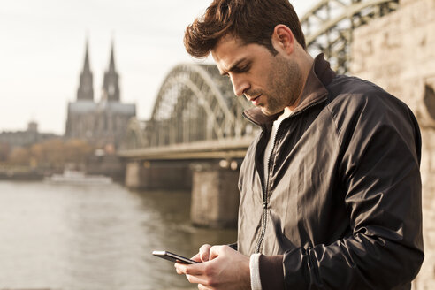 Germany, Cologne, young man with smartphone - FEXF000267