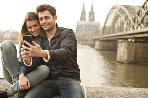 Germany, Cologne, young couple taking selfie in front of Cologne Cathredral - FEXF000276