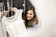 Portrait of smiling young woman showing wedding dress - FEXF000279