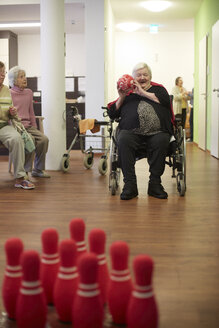 Age demented senior woman bowling with foam ball in a nursing home - DHL000505