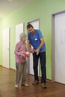 Geriatric nurse talking to age demented senior woman with foam ball  in a nursing home - DHL000508