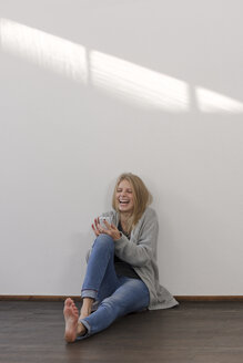 Laughing young woman with smartphone - LAF001277