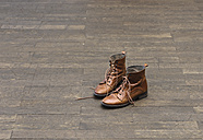 Pair of brown boots on wooden floor - LAF001278