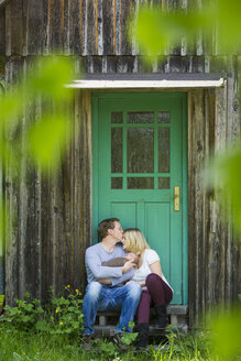 Happy couple with newborn sitting in front of house - JTLF000028