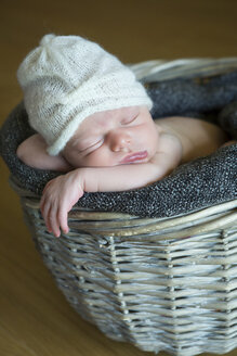 Portrait of sleeping newborn in a wickerbasket wearing wooly hat - JTLF000031