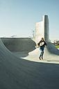 Teenage girl running in skatepark - UUF003041