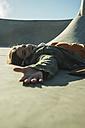 Teenage girl lying in skatepark - UUF003056