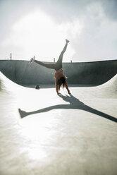 Teenage girl doing a cartwheel in skatepark - UUF003084