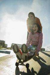 Teenage girl pushing girl on skateboard - UUF003086