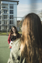 Two teenage girls with soccer ball on sports ground - UUF003075