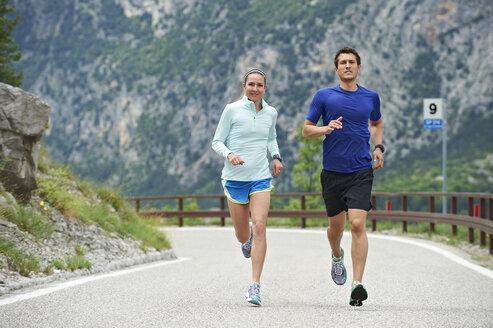 Italy, Trentino, couple running on road near Lake Garda - MRF001457