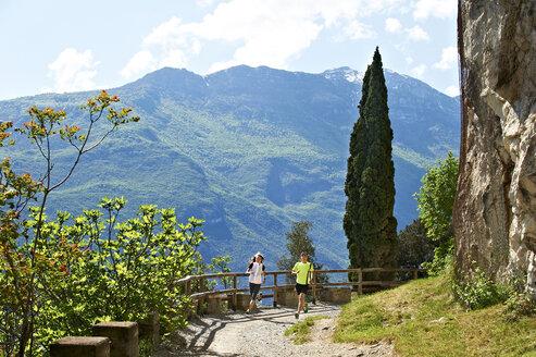 Italy, Trentino, couple running near Lake Garda - MRF001468