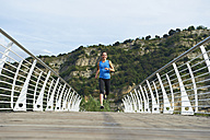 Italy, Trentino, woman running on footbridge near Lake Garda - MRF001479
