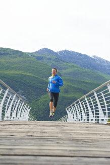 Italy, Trentino, woman running on footbridge near Lake Garda - MRF001482