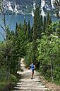 Italy, Trentino, woman running on stairs at Lake Garda - MRF001484