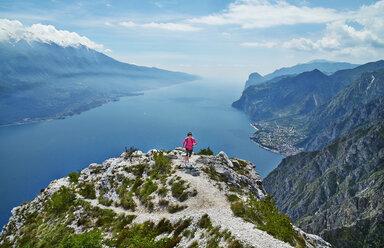 Italy, Trentino, woman running on mountain peak at Lake Garda - MRF001509