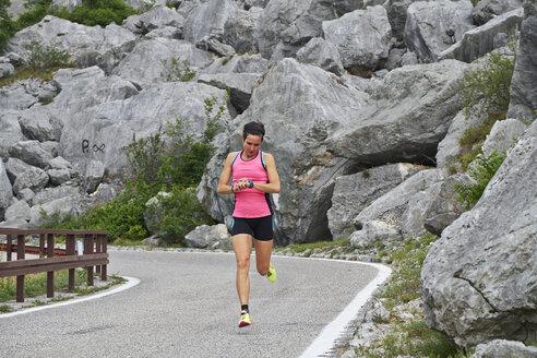 Italy, Trentino, woman running on road near Lake Garda - MRF001514