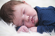 Portrait of baby boy sleeping on sheepskin - ROMF000039