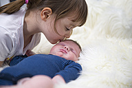 Little girl kissing newborn brother - ROMF000042