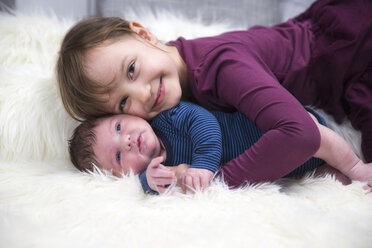 Smiling little girl with newborn brother on sheepskin - ROMF000044