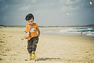 Boy holding sand in his hand, Cronulla beach, New South Wales, Australia - SBD001654