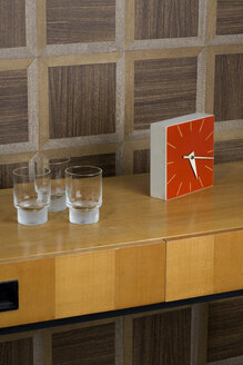 Sideboard with glasses and watch in front of wooden wall cladding - PATF000022