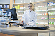 Young pharmacist in pharmacy stamping prescription - SGF001306