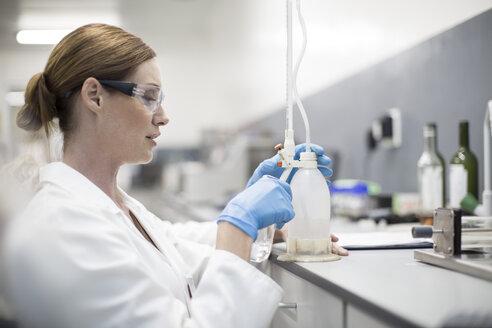Scientist in lab working with liquid - ZEF004235