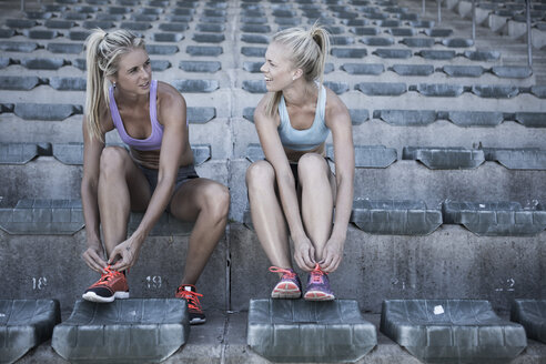 Two sportswomen sitting on grandstand of a stadium tying their shoes - ZEF004592