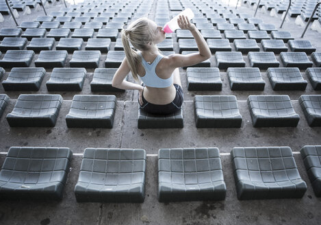 Sportswoman sitting on grandstand of a stadium drinking water - ZEF004594