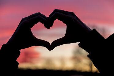 Germany, Baden-Wuerttemberg, Baden-Baden, hands shaping a heart at sunset - JUNF000191