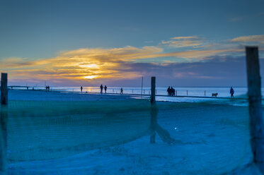 Germany, Lower Saxony, Norden-Norddeich, North Sea coast at sunset with fishing nets on beach - FRF000175
