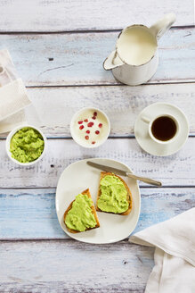 Bread with avocado cream, yogurt with pomegranate seeds and cup of coffee - LVF002663