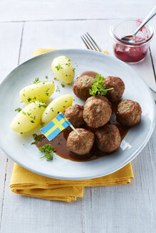 Koettbullar, Swedish meatballs with potatoes and sauce on plate, cowberries - KSWF001352