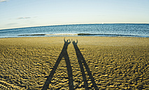 Spain, Valencia, shadow play of two persong on the beach - UUF003099