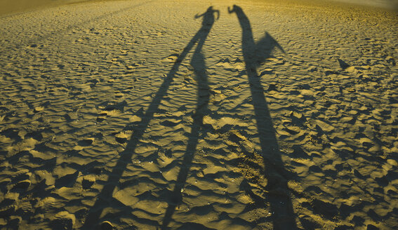Spain, Valencia, shadow play of two persong on the beach - UUF003201