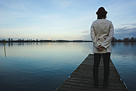 Germany, Roxheim, woman standing on wooden boardwalk at water - UUF003091