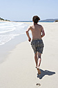 Greece, Elafonisos, young man running on sandy beach - WWF003602