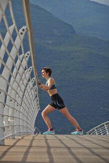 Italy, Trentino, woman stretching on bridge at Lake Garda - MRF001524