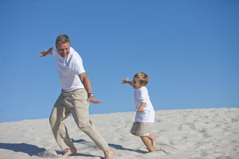 Playful father and son in sand - ZEF004767