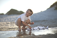Boy playing with paper boats at a water pool on a sandy beach - ZEF004782