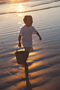 Boy carrying a bucket of water on a sandy beach - ZEF004795