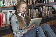 Female student sitting in library looking at digital tablet - ZEF004361
