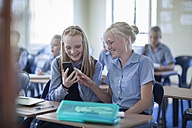 Two smiling schoolgirls in classroom looking at cell phone - ZEF004979