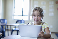 Portrait of smiling primary schoolgirl with digital tablet - ZEF004981