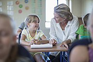 Smiling teacher and schoolgirl in classroom - ZEF004987