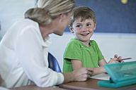 Smiling teacher and schoolboy in classroom - ZEF004989