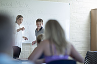 Teacher in classroom with schoolboy at whiteboard - ZEF005001