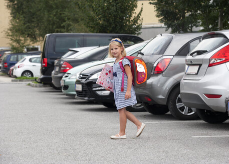 Little girl on her school way crossing parking area - WWF003670