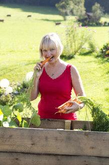 Austria, Mondsee, portrait of woman eating carrot - WWF003631